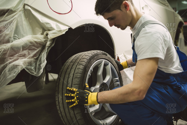 Mechanic changing car tire in his workshop