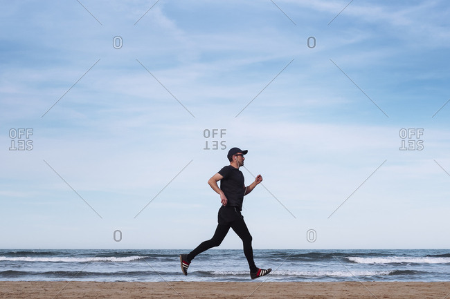 Spain- man dressed in black jogging on the beach