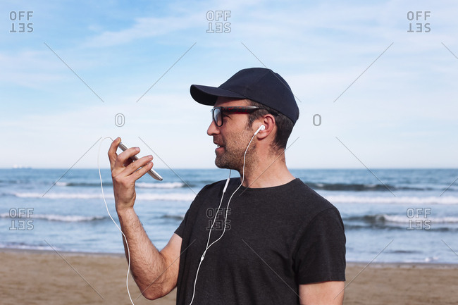Man using smartphone and earphones on the beach