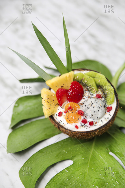 Coconut bowl with various fruits- natural yoghurt and seeds on leaf