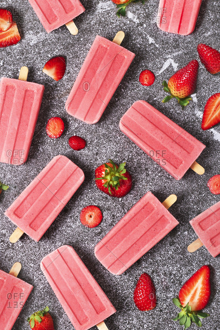 Homemade strawberry ice lollies and strawberries on marble