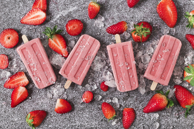 Four homemade strawberry ice lollies- ice and strawberries on marble