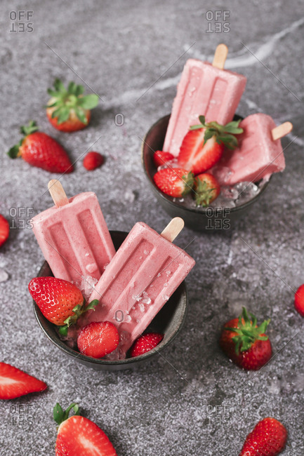 Homemade strawberry ice lollies in bowls