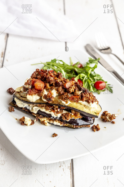 Aubergine lasagna on plate- rucola and tomato- vegetarian