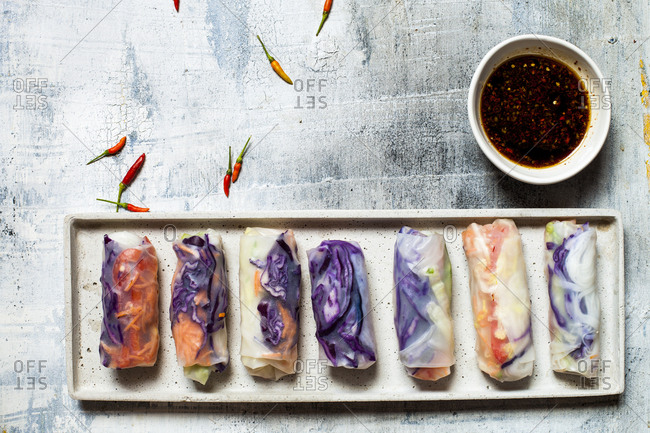 Vegan rice paper wraps (vietnamese summer rolls)- filled with cabbage- carrots- bell pepper- rice noodles- and dipping sauce