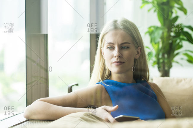 Portrait of attractive woman relaxing on couch at home