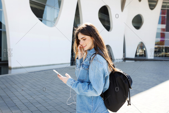 Spain- Barcelona- smiling young woman with backpack listening music with cell phone and earphones