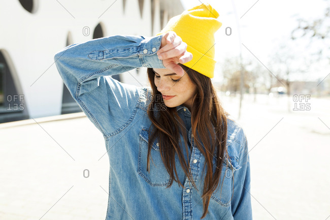 Spain- Barcelona- young woman wearing yellow cap and denim shirt