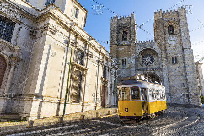 Portugal- Lisbon- typical yellow tram in front of the Cathedral