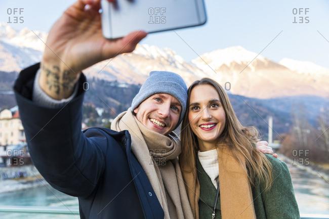 Austria- Innsbruck- portrait of happy young couple taking selfie with smartphone in winter