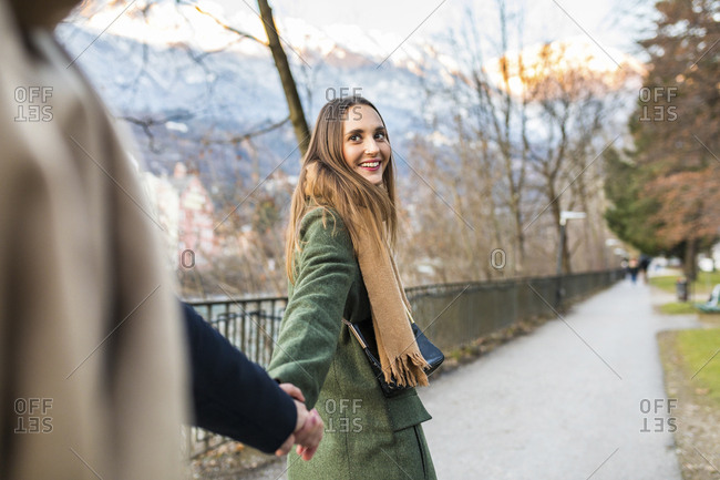 Austria- Innsbruck- portrait of happy young woman strolling hand in hand with her boyfriend at winter time