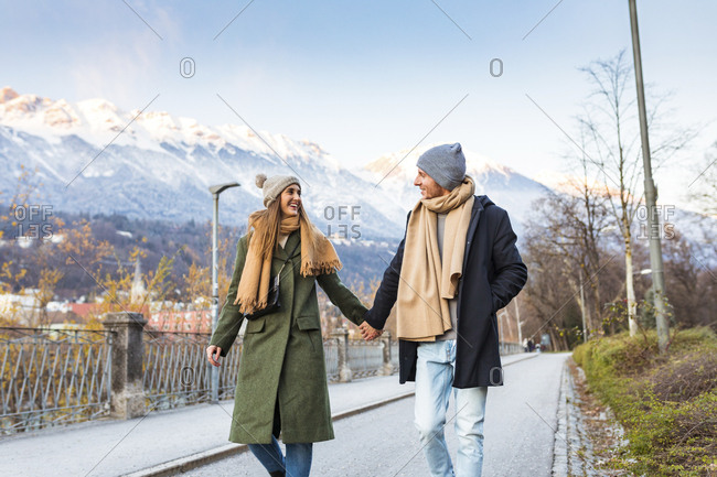 Austria- Innsbruck- happy young couple strolling together hand in hand at winter time