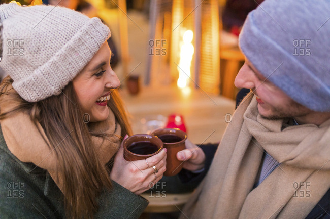Happy young couple drinking mulled wine at Christmas market