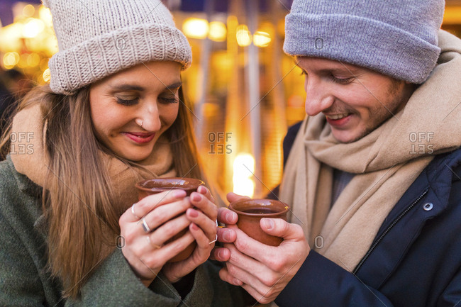 Happy young couple with cups of mulled wine at Christmas market