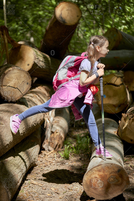 Girl balancing on logs in forest