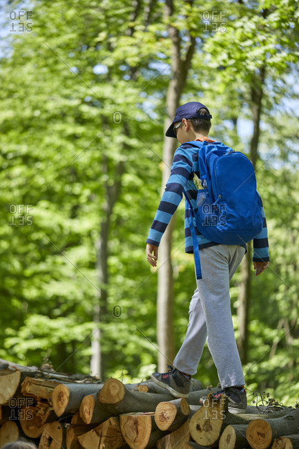 Boy with backpack balancing on logs in forest
