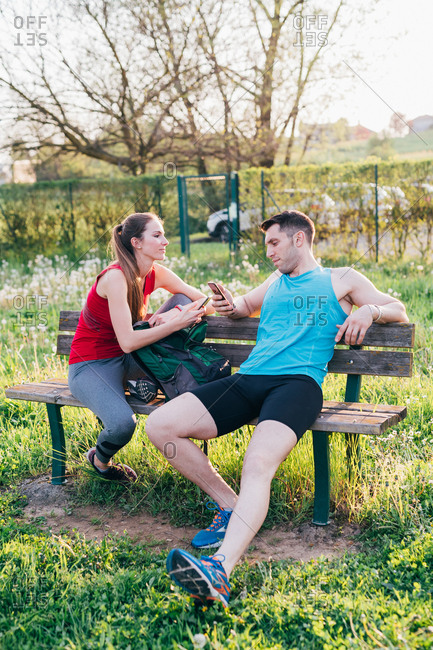 Young couple relaxing after training and using a smart phone