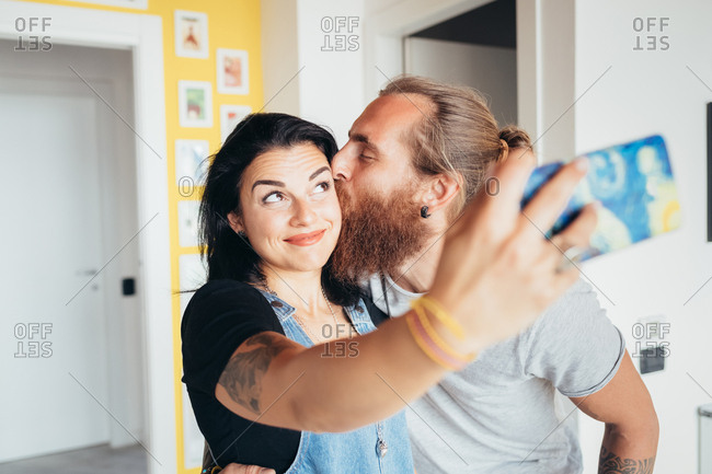 Young couple takes a selfie while smiling and kissing on the cheek