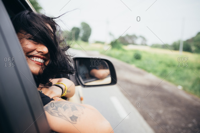 Laughing young woman leans out of a car window
