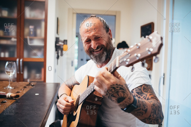 Middle age man playing guitar and laughing indoors
