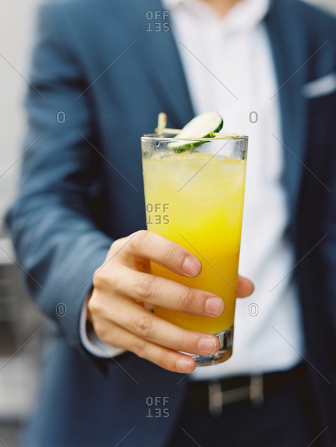 Man holding orange cocktail