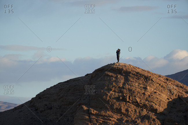 Death Valley National Park, California - February 23, 2018: Photographer standing on hills in Death Valley at sunrise