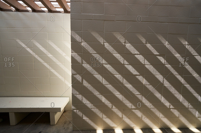 Sunlight shining through slats over cement brick wall