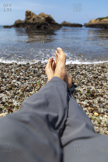 A man's bare feet resting on the coast at Glass Beach in Fort Bragg