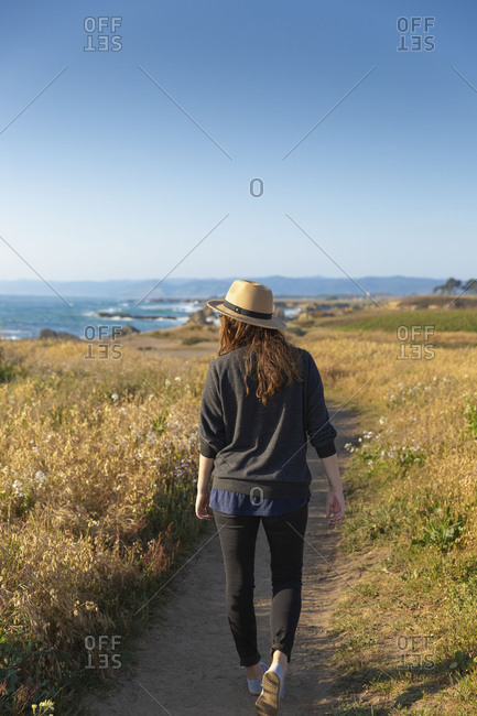 A stylish woman in her twenties wearing a hat and enjoying sunset along the northern California coastline on a warm spring day