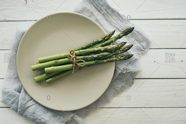 Asparagus on a plate tied with twine on a white table