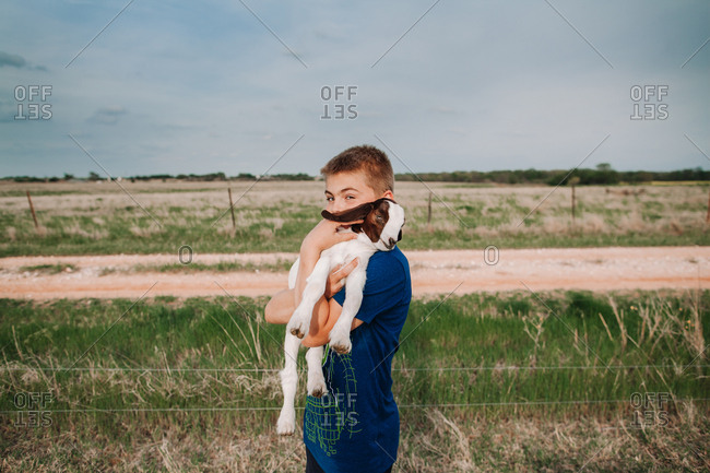 A boy holding a baby goat in a pasture