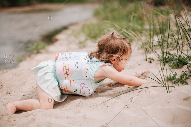 A little girl crawls on a sandy beach