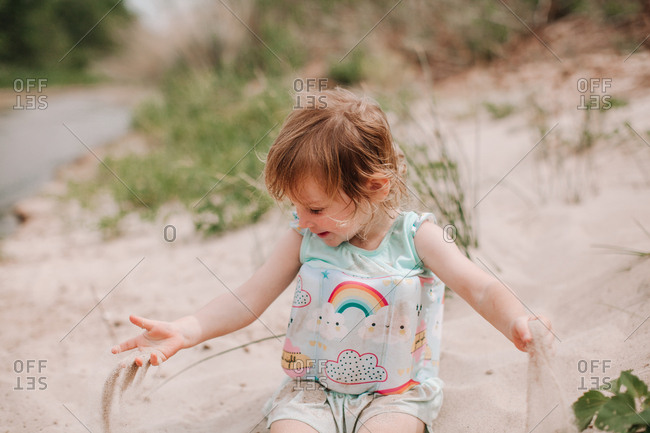 A little girl plays on a sandy beach