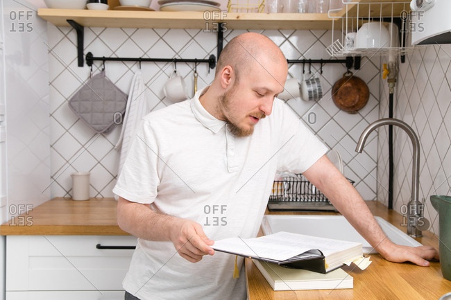 Young bald-headed man with mustache and beard reading a cookbook at the home kitchen. Male cooking style concept