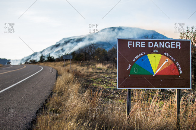 Fire danger sign with smoke from a wildfire in the mountains