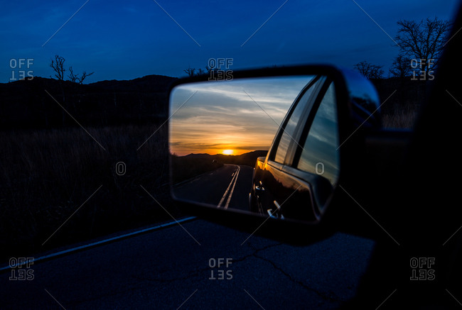 Sunset and highway reflected in car's side mirror