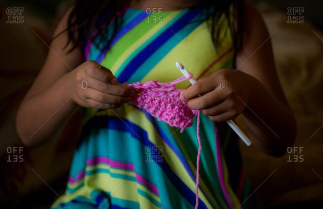 Girl crocheting with pink yarn