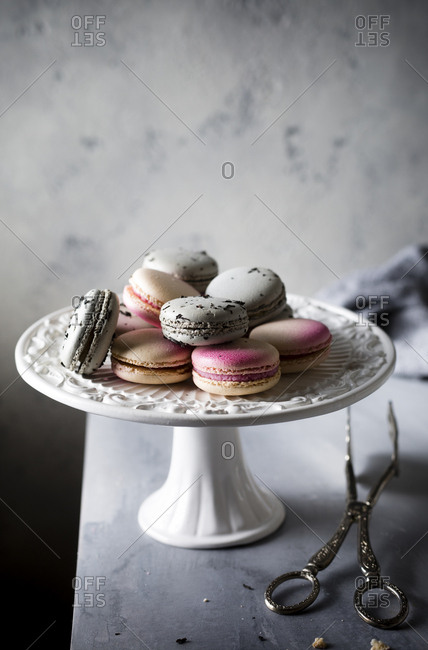 Freshly baked macarons served on a ceramic cake stand with vintage server