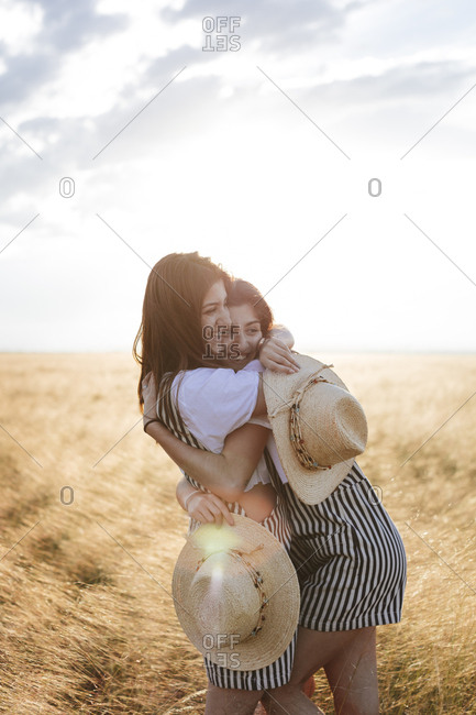 Twin sisters in matching outfits laughing and hugging in wheat field