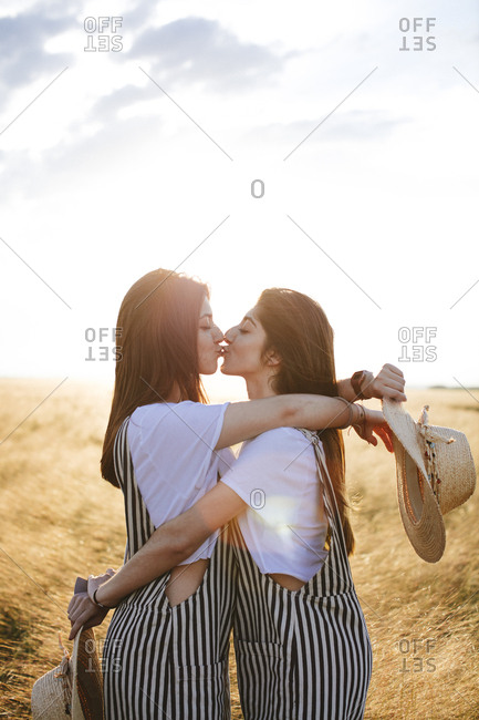 Side view of two female twins hugging and kissing in wheat field