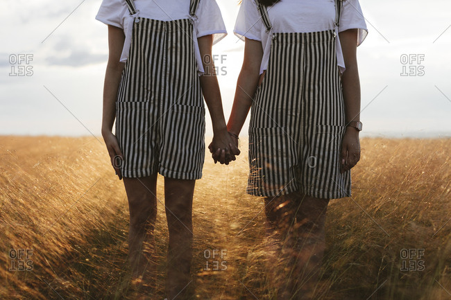 Two women standing side by side wearing matching outfits holding hands in wheat field