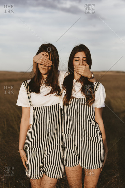 Twin sisters standing side by side covering each others eyes and mouth in field