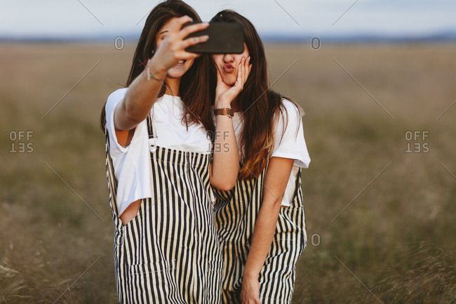 Two women in field wearing matching clothes taking selfie and goofing around