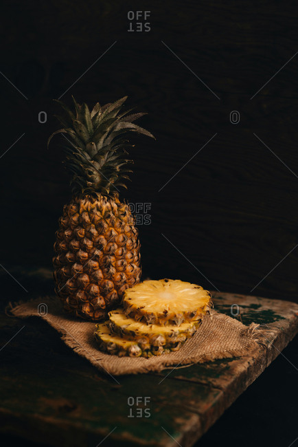Cutting fresh pineapple on wooden table