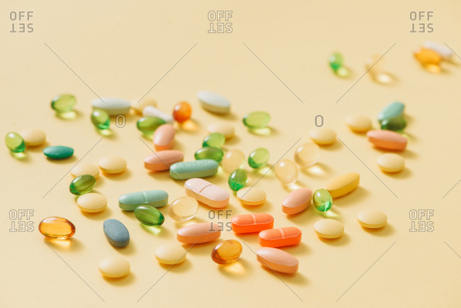 Various kinds and different colors of pills. Medicine on yellow background