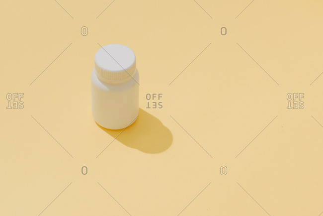 The bottle of pills on yellow background.