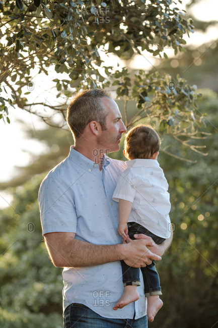 Close-up of thoughtful father carrying son while standing against trees at park