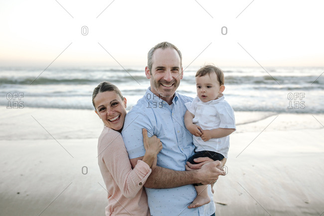 Portrait of happy parents with son enjoying at beach against clear sky during sunset