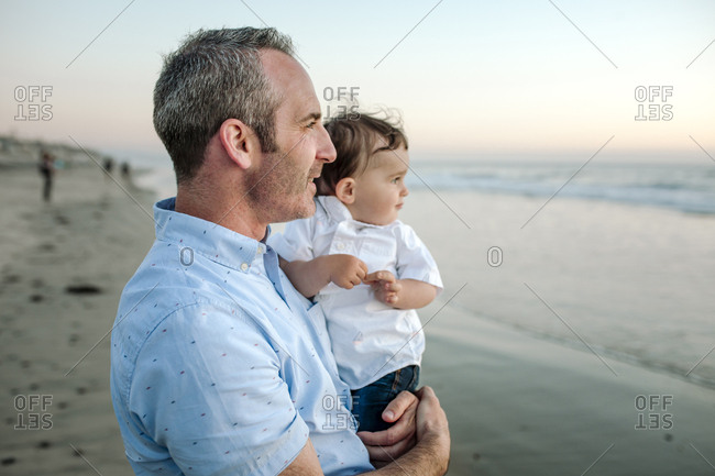 Father and son looking at sea while standing on shore against sky during sunset