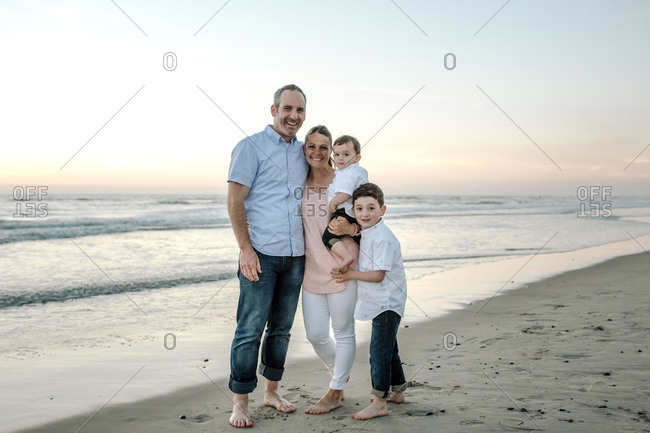 Portrait of happy family standing at beach against clear sky during sunset